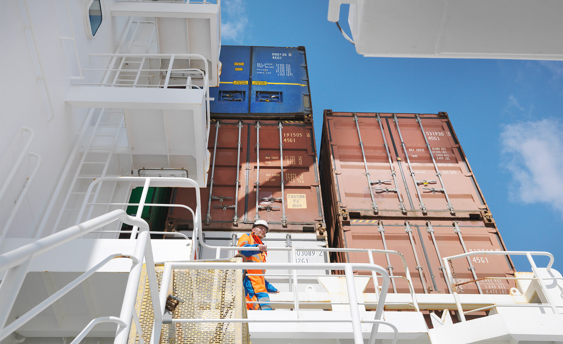 A person walks around on a cargo ship fully loaded with containers