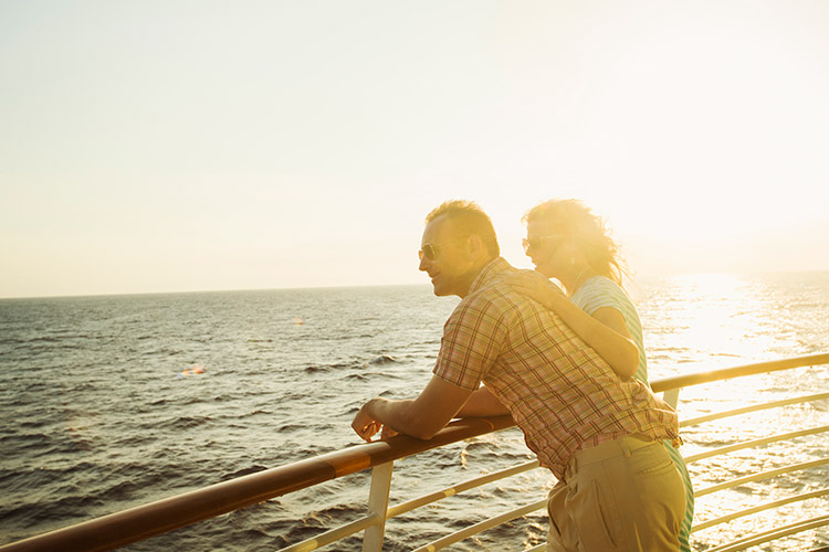A couple - woman and man - at the railing of a luxury cruise ship
