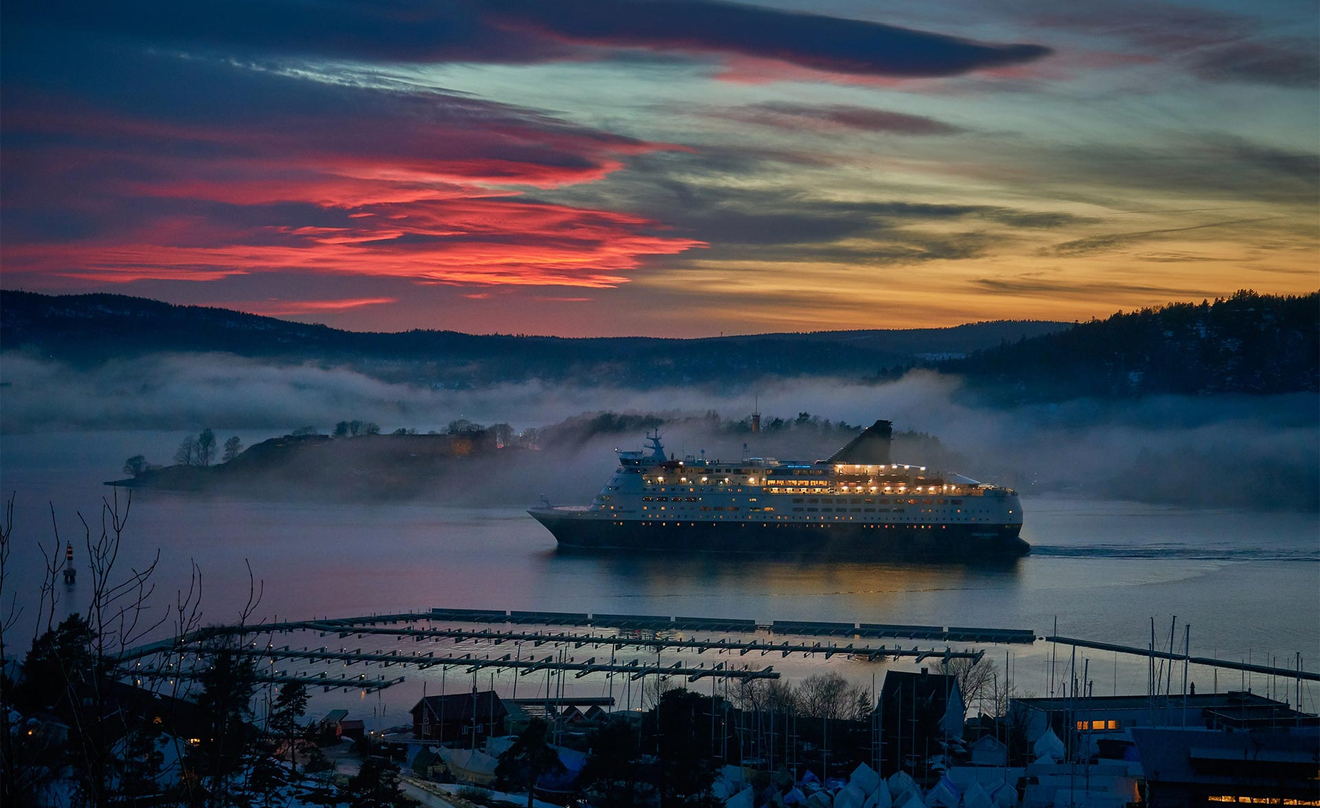 A marine cruise ship sails at dusk on a Norwegian fjord