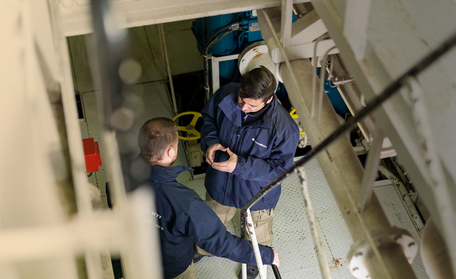 Two technicians at Consilium discussing the installation of a fire detector