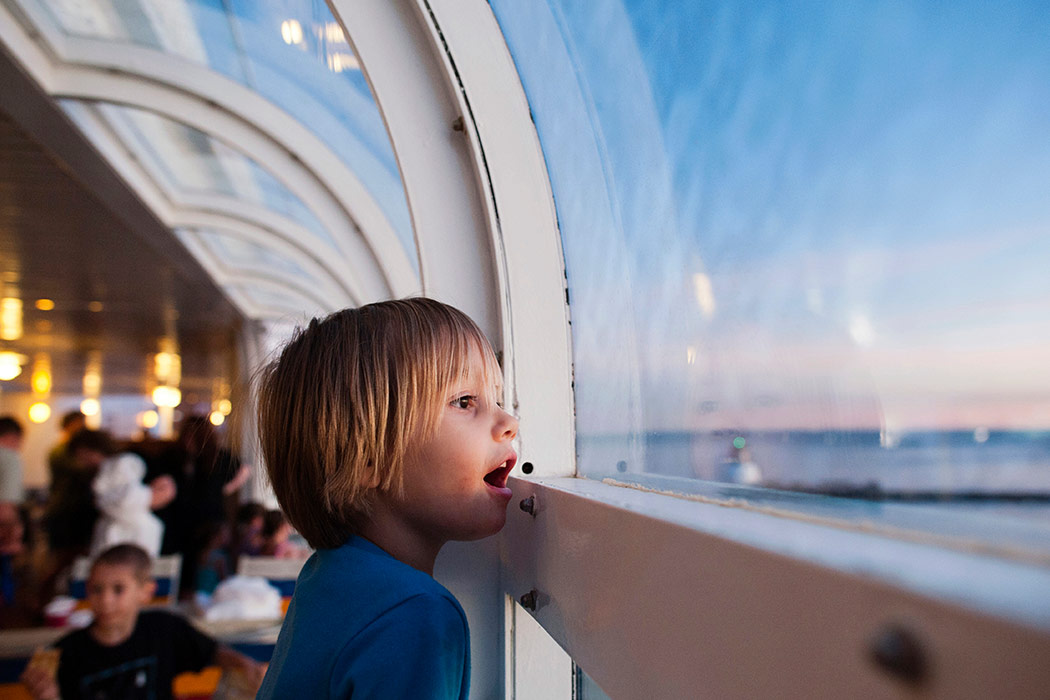 A boy on a cruise ship looking out the window